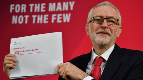 Labour party leader Jeremy Corbyn holds up a document during a press conference in London © AFP / Ben Stansall