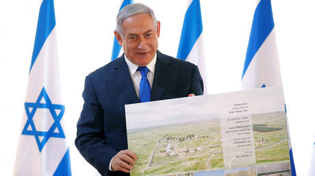 FILE PHOTO: Benjamin Netanyahu poses with a placard given while visiting a Jordan Valley settlement © REUTERS/Amir Cohen