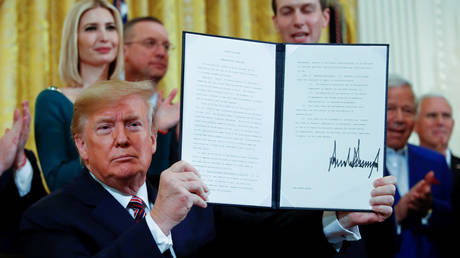 US President Donald Trump holds up an executive order on anti-semitism that he signed during a Hanukkah reception at the White House