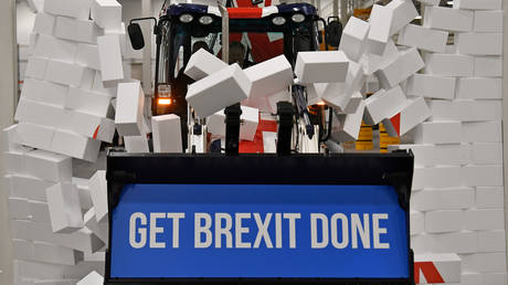 """Britain's PM and Conservative leader Boris Johnson drives a Union flag-themed JCB, with the words """"Get Brexit Done"""" inside the digger bucket, through a fake wall emblazoned with the word """"GRIDLOCK"""""""