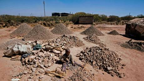 A child breaks rocks extracted from a cobalt mining at a copper mine quarry and cobalt pit in Lubumbashi, Congo