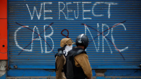 Police officers walk past a graffiti during a protest against a new citizenship law. ©REUTERS/Adnan Abidi