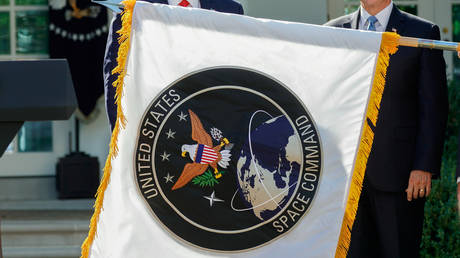 US President Donald Trump stands behind a U.S. Space Command flag with Vice President Mike Pence