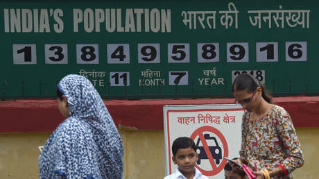An Indian woman waits with school children for their bus in front of a 'population clock' showing India's population, on World Populatiuon Day in Mumbai on July 11, 2018.