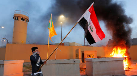 A protester holds an Iraqi flag outside the main gate of the US Embassy in Baghdad, Iraq December 31, 2019.