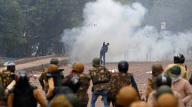 Tear gas fired as protesters hurl stones at police & damage cars in New Delhi in massive rally over citizenship bill (VIDEO)