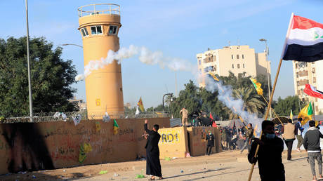Protesters and militia fighters throw back a tear gas canister used by U.S. Embassy security men during a protest to condemn air strikes on bases belonging to Hashd al-Shaabi (paramilitary forces), outside the embassy in Baghdad, Iraq January 1, 2020.