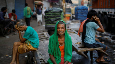 FILE PHOTO: Migrant laborers sit on a handcart as they wait for work at a wholesale market in the old quarters of Delhi, India.