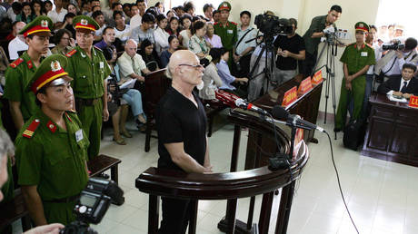 A policeman watches former British rock star Gary Glitter standing trial in a Vietnamese court, on charges of child sex abuse © AFP / HOANG DINH NAM