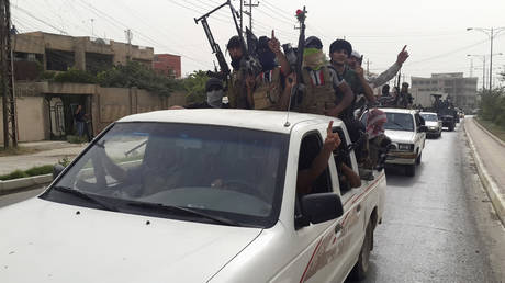 FILE PHOTO: IS terrorist fighters celebrate on vehicles plundered from Iraqi security forces in Mosul, June 12, 2014