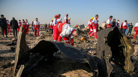 Red Crescent workers check the debris from the Ukraine International Airlines plane on the outskirts of Tehran