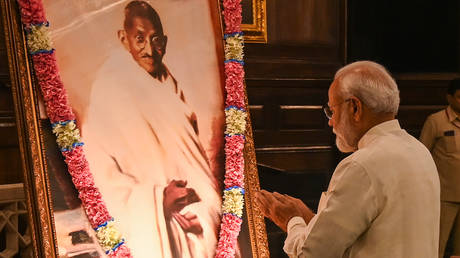 India's Prime Minister Narendra Modi gestures beside a portrait of Mahatma Gandhi in New Delhi on October 2, 2019. © AFP / Money Sharma