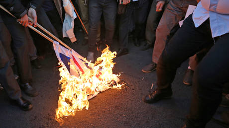 Iranian demonstrators set alight a Union Jack in front of the British embassy in  Tehran on January 12, 2020.
