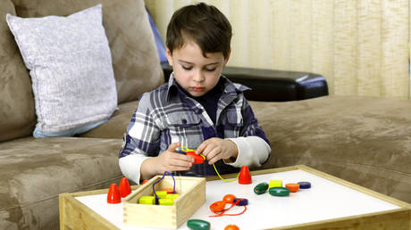 Boy with autism stringing together large beads that are easy to grasp.