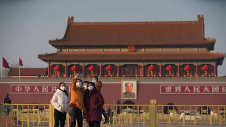 Visitors wearing masks take selfies in front of Beijing's Tiananmen Gate, January 30, 2020 © Reuters / Stringer