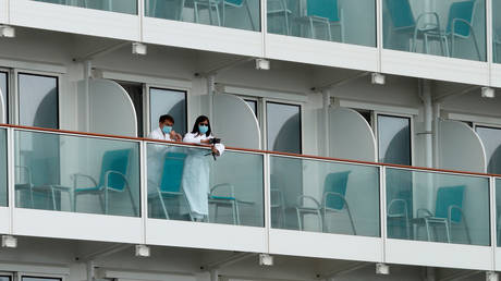 Passengers look out from a cabin of the World Dream cruise ship in Hong Kong, China February 6, 2020.