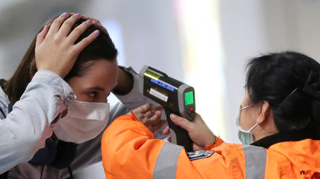 FILE PHOTO: A worker checks the temperature of a passenger arriving into Hong Kong International Airport with an infrared thermometer, following the coronavirus outbreak in China.