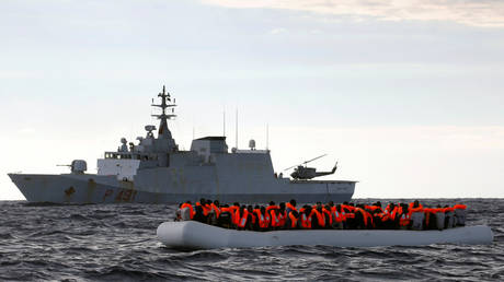 FILE PHOTO: An overcrowded raft carrying African migrants is seen in front of an Italian Navy vessel in 2017 © REUTERS/Yannis Behrakis