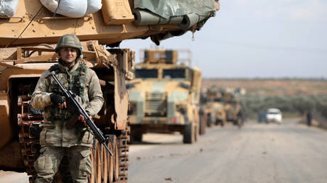 A Turkish soldier stands in front of a military vehicles convoy east of Idlib city in northwestern Syria on February 20, 2020