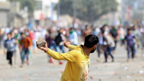 A man throws a stone at rival demonstrators during a clash over a new citizenship law in New Delhi, India, February 24, 2020.