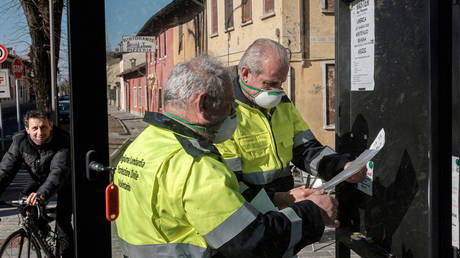 Civil protection officers wearing protective masks put up posters in San Fiorano, Italy © Reuters / Marzio Toniolo