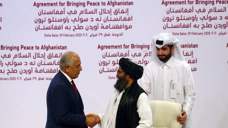 Mullah Abdul Ghani Baradar, the leader of the Taliban delegation, and Zalmay Khalilzad, US envoy for peace in Afghanistan, shake hands after signing a peace agreement in Doha, Qatar. February 29, 2020. © Reuters / Ibraheem al Omari