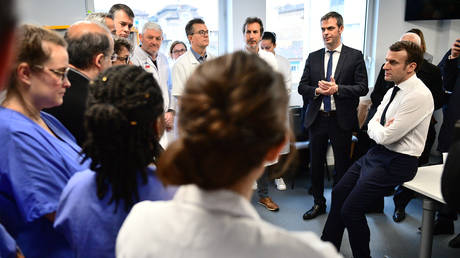 French President Emmanuel Macron visits a Paris hospital where a patient infected with COVID-19 has died. February 27, 2020.