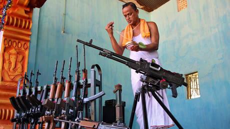 FILE PHOTO: A Hindu priest worships next to weapons belonging to Tripura State Rifles in Agartala, India, September 18, 2019 © Reuters / Jayanta Dey