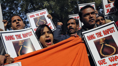 FILE PHOTO People shout slogans and hold placards during a protest in New Delhi December 29, 2012. © REUTERS/Adnan Abid