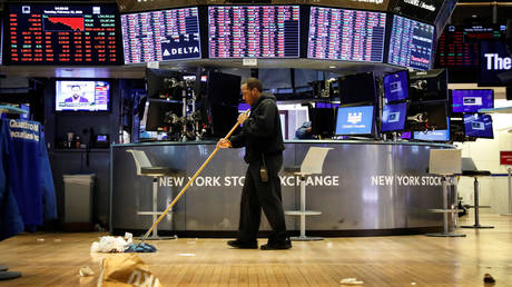 A worker cleans up after traders on the floor of the New York Stock Exchange after the closing bell