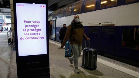 A man walks past a coronavirus information board at Montparnasse train station, Paris ©  Reuters / GONZALO FUENTES