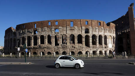 A Fiat 500 in front of the ancient Colosseum in Rome, Italy