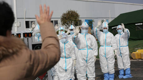 FILE PHOTO. Medical personnel in protective suits wave hands to a patient who is discharged from the Leishenshan Hospital in Wuhan. ©China Daily via REUTERS