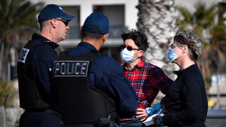 FILE PHOTO. French police officers control two women wearing face masks in Marseille. © AFP / Gerard Julien