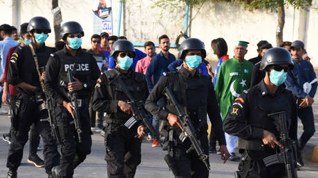 FILE PHOTO: Police officers wear masks amid coronavirus fears, as they guard Pakistan Super League cricket matches outside the National Stadium in Karachi, Pakistan.