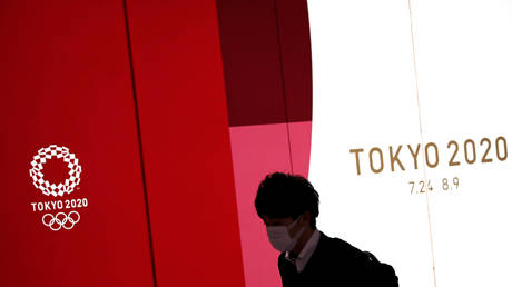 A man wearing a protective face mask, following an outbreak of the coronavirus disease (COVID-19), walks past the upcoming Tokyo 2020 Olympics decoration board in Tokyo, Japan, March 23, 2020.