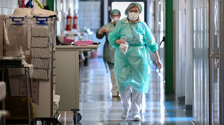 Medical workers wearing protective masks and suits walk in an intensive care unit at the Oglio Po hospital, where patients suffering from coronavirus disease (COVID-19) are treated, in Cremona, Italy March 19, 2020