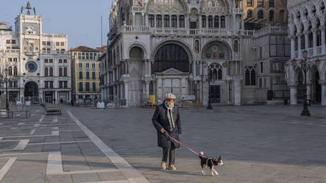 An elderly person walks in an empty Piazza San Marco with his dog on March 11, 2020
