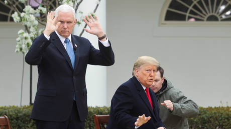 """US Vice President Mike Pence (left) and President Donald Trump prepare for a Fox News """"virtual town hall"""" on the coronavirus outbreak at the White House, March 24, 2020."""