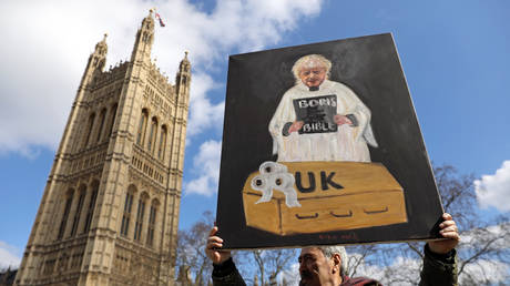 Artist Kaya Mar holds a painting depicting Britain's Prime Minister Boris Johnson, outside Houses of Parliament, following an outbreak of the coronavirus, in London, Britain March 16, 2020.