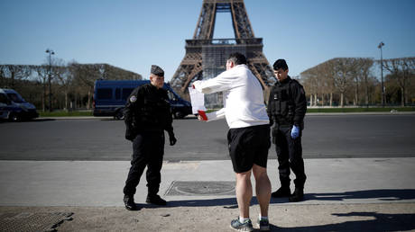 French Gendarmes control a man near the Eiffel tower in Paris as a lockdown is imposed © Reuters / Benoit Tessier