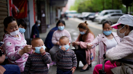 Children and women wearing face masks are seen in Xianning, after the lockdown was lifted in Hubei province, the epicenter of China's coronavirus outbreak, March 26, 2020.