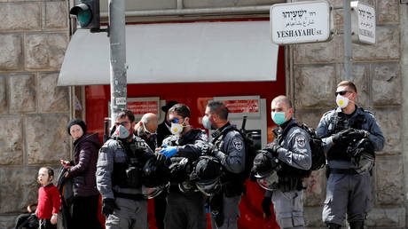 Israeli policemen stand together as they enforce government restrictions to fight the spread of the coronavirus disease (COVID-19) in the ultra-Orthodox Jewish neighborhood of Mea Shearim in Jerusalem March 24, 2020.