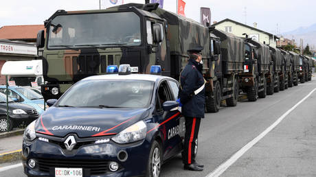 Carabinieri military police officer stands guard as military trucks wait to take away coffins in Seriate, Italy, March 25, 2020.