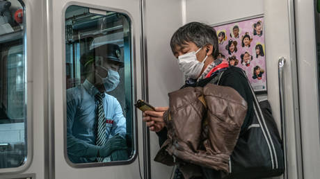 A train guard and passenger both wear face masks as they ride the Yamanote Line on March 27, 2020 in Tokyo, Japan