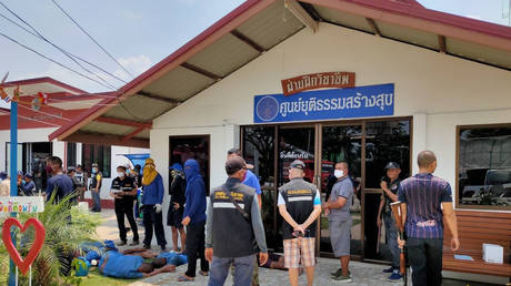 Buriram Prison security personnel looking over a group of inmates on the ground after a jail riot in Buriram. March 29, 2020 © Thailand Ministry of Justice via AFP