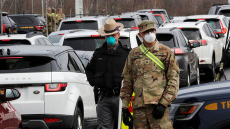 US Military personnel and police stand amid a line of cars of people arriving for testing at a drive-thru coronavirus disease testing center in Staten Island New York. © Reuters / Mike Segar