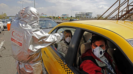 Members of the Iranian Red Crescent test people for coronavirus Covid-19 symptoms outside Tehran on March 26, 2020 © STR / AFP