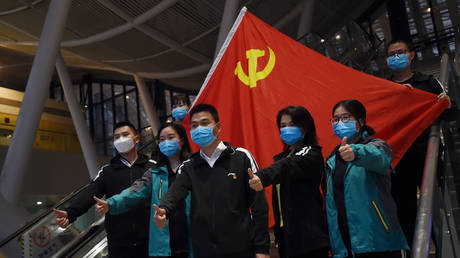 FILE PHOTO. Medical workers from outside Wuhan pose for pictures with a Chinese Communist Party flag. ©REUTERS / Stringer