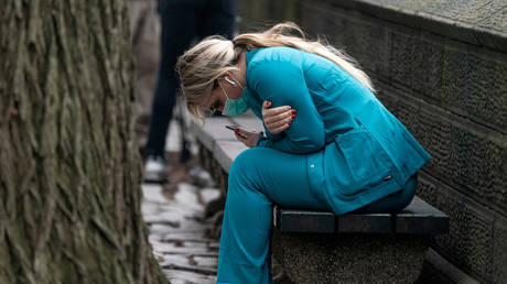 A healthcare worker sits on a bench near Central park in Manhattan, New York City, March 30, 2020.